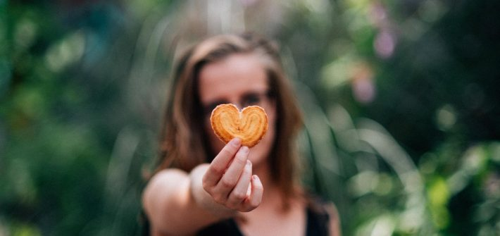 woman in black top holding a heart shaped cookie