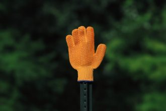 orange glove gesturing stop with greenery background