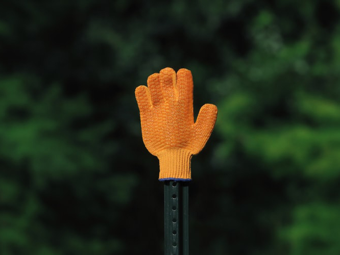 orange glove gesturing stop with greenery background