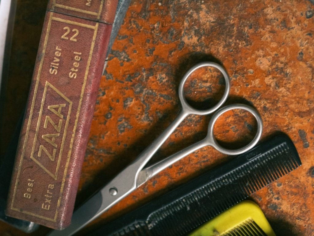 barbers scissors and combs on orange background