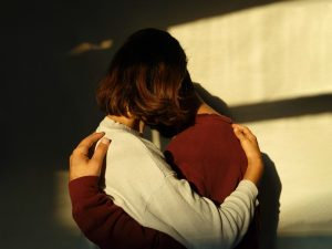 two persons hugging