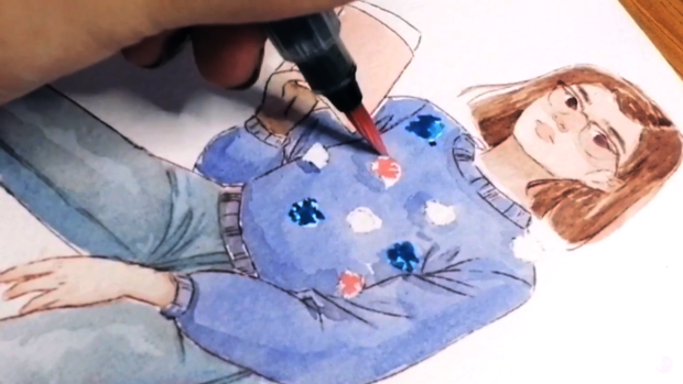 Picture of a watercolor painting of a brunette with shoulder-length hair wearing a big glasses and blue sweather with multi-colored fuzzy balls. A hand holding a water brush pen with pink paint is in the process of coloring in a fuzzy ball. This is a self-portrait.